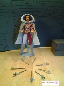 Image of Barbie doll in Medieval cloak, holding a sword.