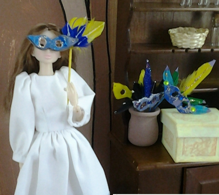 Photo of a doll holding a Mardi Gras mask that was hand-made