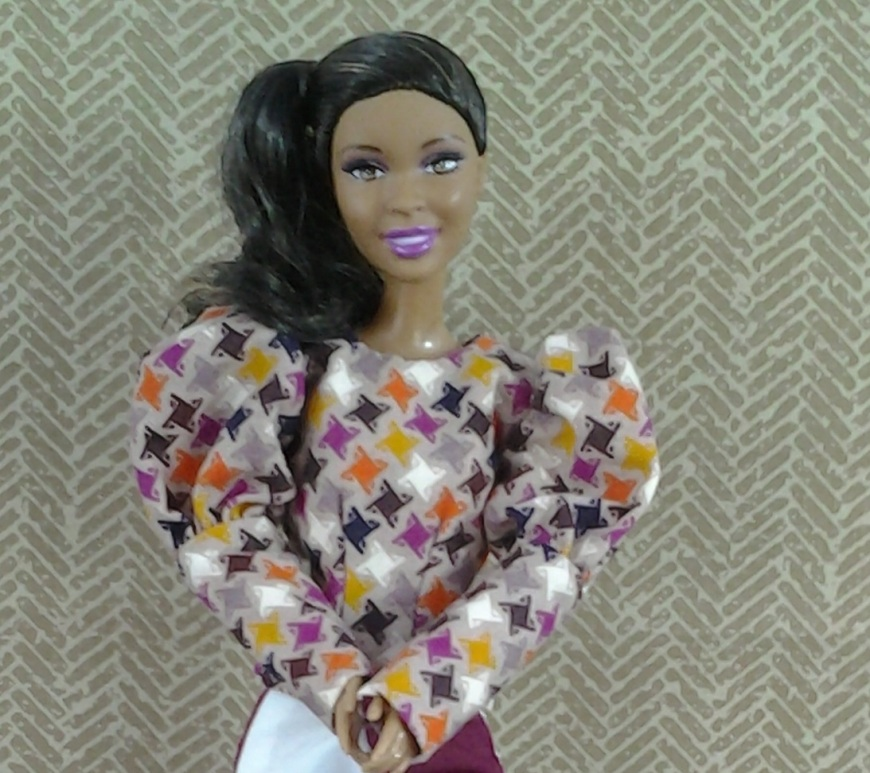 Image of Barbie doll dressed in poofy-sleeve shirt with diamond pattern