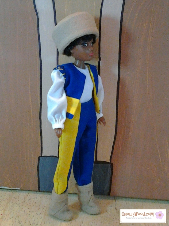 Image of African American doll with natural afro hair under a cap. Doll is wearing medieval garb.