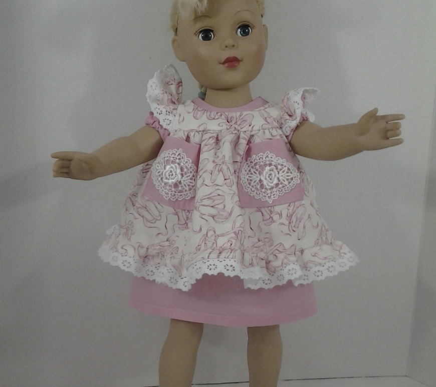 Image of AG doll wearing dress with lacy pinafore