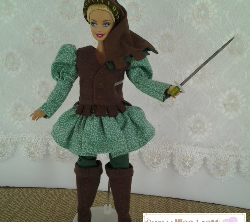 Image of Barbie doll in medieval male costume, holding sword aloft.