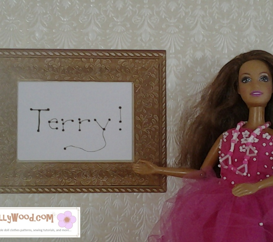 "Image of Barbie in fancy prom-style dress pointing at a framed name, ""Terry"""
