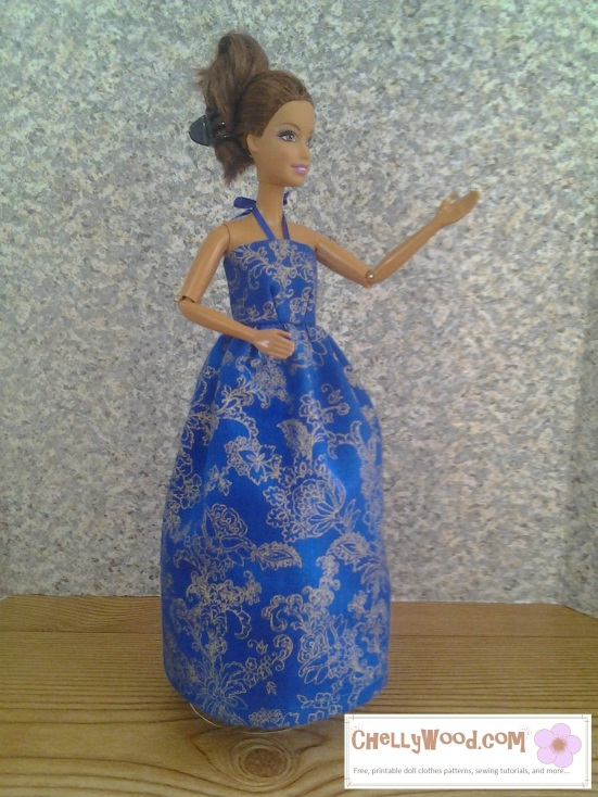 """Image of """"Teresa"""" style Barbie doll dressed in handmade blue gown with gold designs. It's in a halter-style with a ribbon that attaches the bodice around the neck. At the bottom of the image it says, """"chellywood.com free tutorials, doll clothes patterns, and more."""""""
