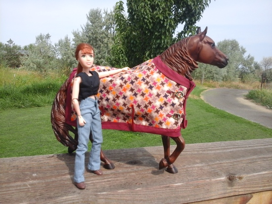 Image of Breyer doll standing near Top Sails Rainmaker model horse. The horse is covered by a handmade multi-colored horse blanket framed by a bias tape edging.
