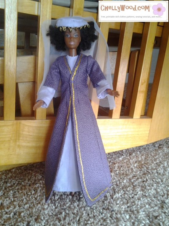 Image of dark-complected Barbie doll wearing sherwal and overcoat in traditional Lebanese costume style. She also wears a veil with round, flat beads hanging from the brow area.