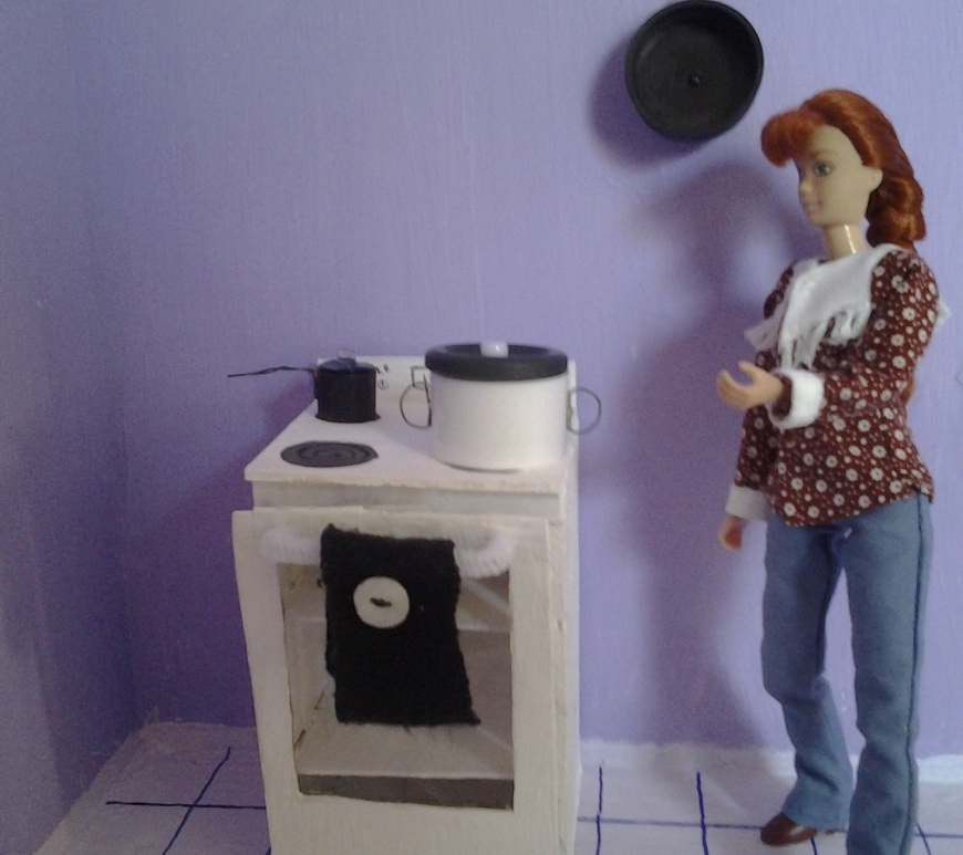 Image of traditional Breyer doll standing in a kitchen, wearing Western shirt and jeans. Also standing nearby is a hand-made stove with handmade miniature pots and pans