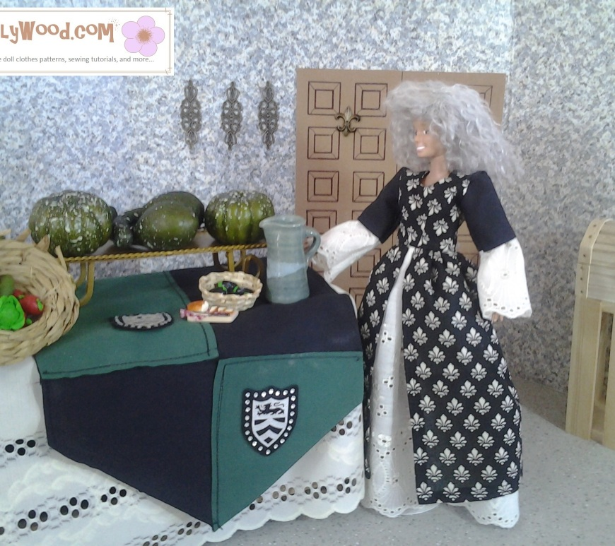 Image of Barbie doll wearing gray wig and standing before a table laden with gourds and a cornucopia of food.