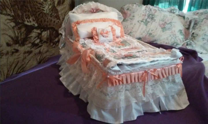 Image of elegant doll bed with ribbons and bows