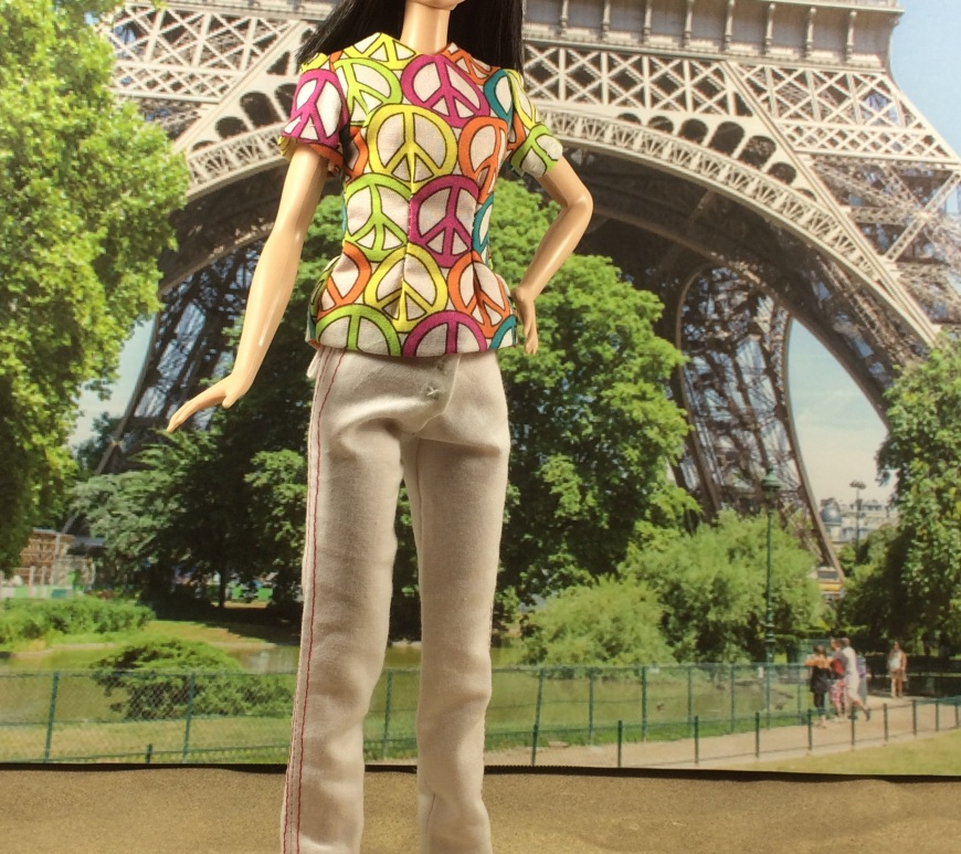 "Image of Mattel's ""Tall Barbie"" standing in front of the Eiffel Tower in Paris, wearing a pair of white handmade pants with red seams. Barbie has one hand on her hip and the other at her side. She smiles brightly. She's also wearing a princess-seams shirt decorated with peace signs. Tall Barbie's features look Asian, and her skin tone is pale. The image includes a watermark that says, ""ChellyWood.com"" for free printable sewing patterns and tutorials."