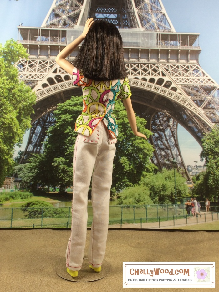 """Image of Mattel's """"Tall Barbie"""" standing in front of the Eiffel Tower in Paris, wearing a pair of white handmade pants with red seams. Barbie has one hand in her hair and the other at her side. She has her back to us, showing the embroidered pockets of her jeans. She's also wearing a princess-seams shirt decorated with peace signs. Her hair is shoulder-length and a dark chocolate color, and her skin tone is pale. The image includes a watermark that says, """"ChellyWood.com"""" for free printable sewing patterns and tutorials."""