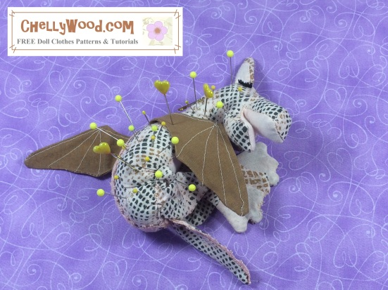 "Image of baby dragon (pin cushion) laying on its belly with sleepy eyes and pins in its back. Overlay says, ""ChellyWood.com: free printable sewing patterns and tutorials"". The baby dragon's facial expression is very sweet in sleep."