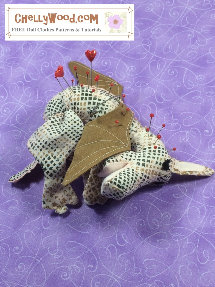 """Image of baby dragon (pin cushion) laying on its belly with sleepy eyes and pins in its back. Overlay says, """"ChellyWood.com: free printable sewing patterns and tutorials"""". Background color is purple with a swirly heart pattern."""