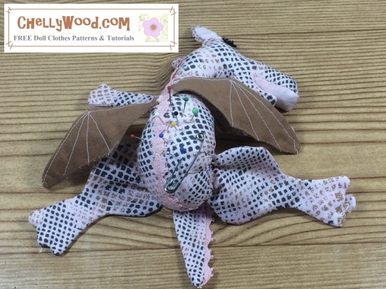 "Image of baby dragon (pin cushion) laying on its belly with sleepy eyes and pins in its back. Overlay says, ""ChellyWood.com: free printable sewing patterns and tutorials"""