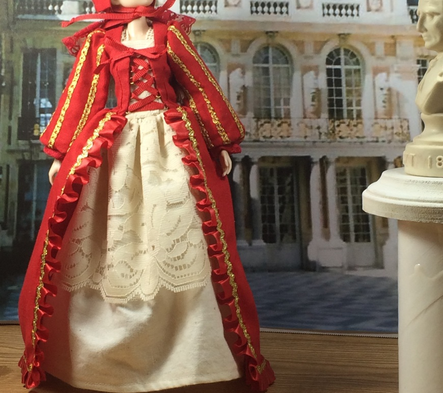"Image of Momoko Doll in Renaissance ball gown, standing in front of the Palace at Verseille, with a bust before her. She wears a Pilgrim-like bonnet and an elegant lace shift as well as the elegant over-dress which has been embellished with gold braided ribbons and rick-rack. Overlay says, ""Chelly Wood Dot Com. Free printable Sewing patterns for dolls and free tutorials."""
