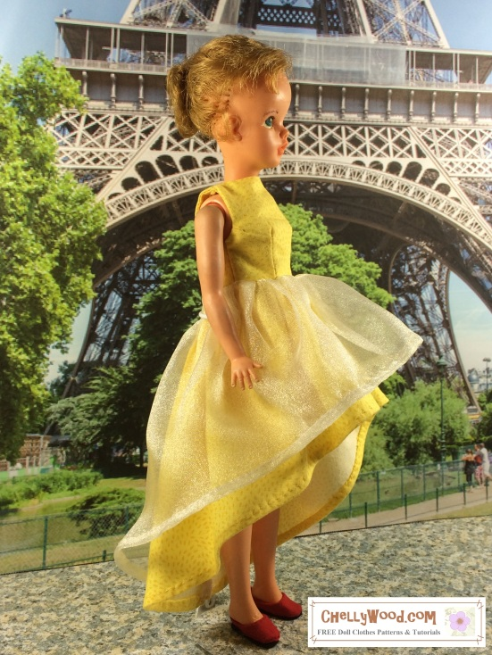 "Image of Ideal's Tammy Doll wearing a modern high-low dress with a tulle decorative over-layer. She stands in front of the Eiffel Tower, and the overlay reads, ""ChellyWood.com: free printable sewing patterns and tutorials."""