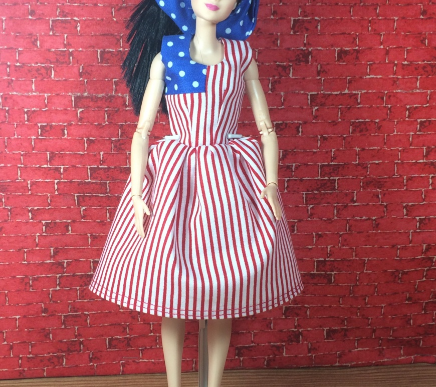 "Visit ChellyWood.com for free, printable sewing patterns to fit dolls of many shapes and sizes. Image shows Made to Move Barbie wearing a handmade dress which looks a lot like a United States Flag. One corner of the dress is made of blue and white polka dot fabric. The rest of the dress is made of red and white stripes. The doll also wears a headscarf made of blue and white polka dots and red, plastic, high-heeled sandals. The bottom corner of the image says, ""Chelly Wood Dot Com: free printable sewing patterns for dolls of many shapes and sizes."""