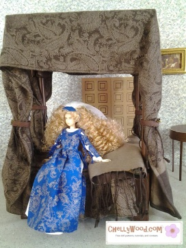 """Visit ChellyWood.com for free, printable sewing patterns to fit dolls of many shapes and sizes. Image shows Japanese Momoko doll sitting on a four-poster bed with velvety bed-curtains. Momoko Doll wears a blue and gold gown with Renaissance lace-up sleeves and a blue and white gauzy veil. Caption says, """"Chelly Wood dot com for free, printable sewing patterns and tutorials."""""""