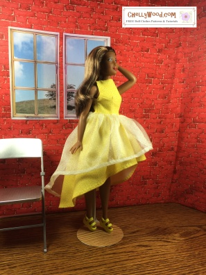 Visit ChellyWood.com for free, printable sewing patterns to fit dolls of many shapes and sizes. Image shows African American Curvy Fashionista Barbie wearing a hand-made high-low dress made of tulle and cotton/polyester-blend yellow fabrics. She holds one hand in her hair, and her strappy high-heel sandals match the yellow dress. Behind her is a doll-sized miniature folding chair and a brick wall with windows opening onto a field wherein stands a lone tree.