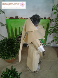 "Visit ChellyWood.com for free, printable sewing patterns for dolls of many shapes and sizes. Image shows Texas A and M Ken doll dressed as Friar Laurence in Shakespeare's Romeo and Juliet. He wears a hooded robe and sandals. He stands in an Italian garden with a cobble-stone path behind him and a small topiary nearby. Caption reads ""Chelly Wood dot come for free, printable sewing patterns and tutorials."""