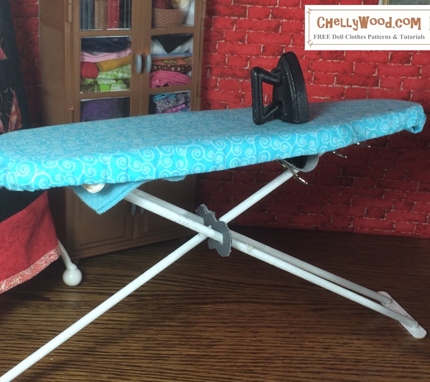 The image shows a hand-made ironing board with cover. The website where you can find the patterns for both the ironing board and it's cover is displayed: ChellyWood.com This ironing board is made to fit 1:6 scale dioramas or dollhouses.