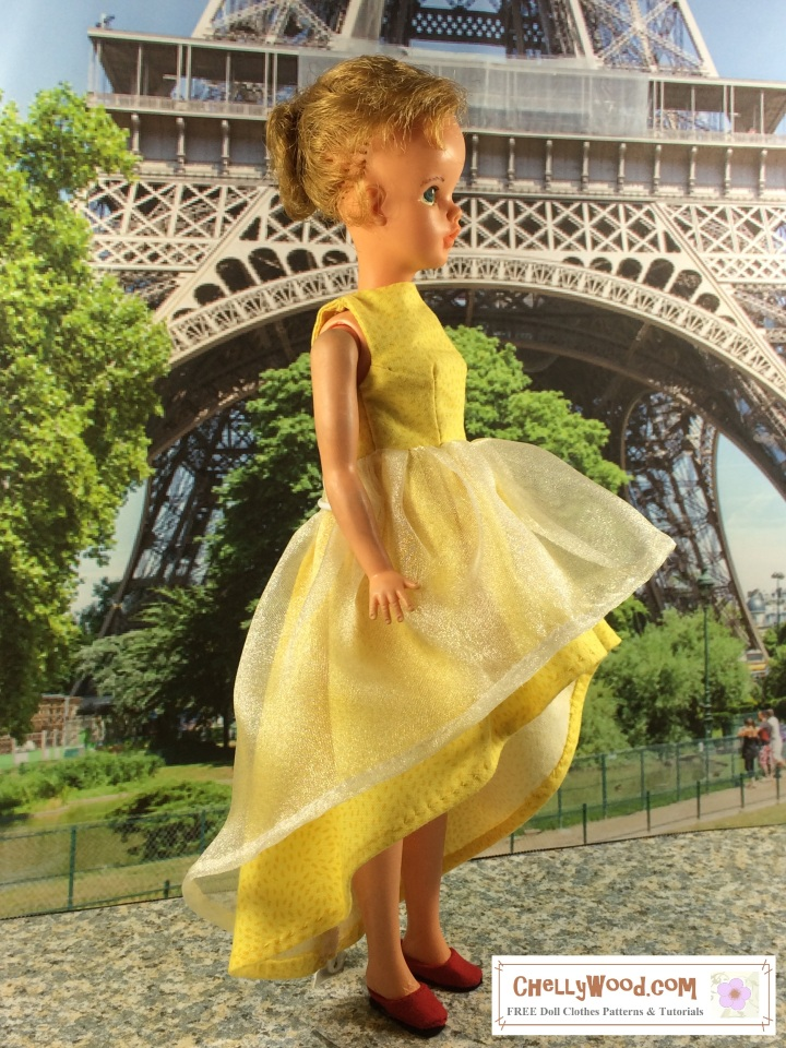 Visit ChellyWood.com for free, printable sewing patterns to fit dolls of many shapes and sizes. Image shows vintage Tammy doll from Ideal wearing a hand-made sleeveless gown with tulle and cotton skirts in a hi-low style. She stands before a diorama-style photo of the Eiffel Tower, taken near its metallic criss-crossed base.