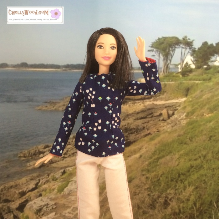 "Visit ChellyWood.com for free, printable sewing patterns to fit dolls of many shapes and sizes at ChellyWood.com. Image shows Mattel's Tall Barbie wearing a long-sleeved navy blue shirt with tiny flowers printed on it and a pair of white jeans. She waves to the camera in front of a beach at Normandy, France. Caption reads, ""Chelly Wood dot com for free, printable sewing patterns and tutorials."""