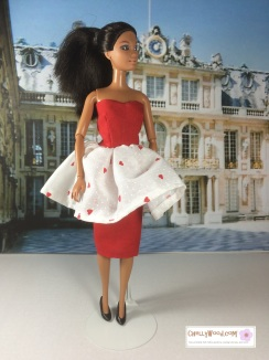 "Visit ChellyWood.com for free, printable sewing patterns for dolls of many shapes and sizes. Image shows African American Barbie doll wearing red strapless dress with a white valentine-print flouncy skirt atop a red pencil skirt (layers of skirt are shown). The doll stands in the courtyard at Verseilles in Paris, France. She wears black high-heel pumps. Watermark says, ""Chelly Wood dot com for free, printable sewing patterns to fit dolls of many shapes and sizes."""