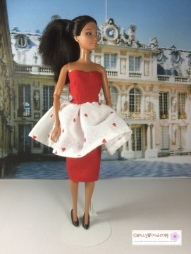 """Visit ChellyWood.com for free, printable sewing patterns for dolls of many shapes and sizes. Image shows African American Barbie doll wearing red strapless dress with a white valentine-print flouncy skirt atop a red pencil skirt (layers of skirt are shown). The doll stands in the courtyard at Verseilles in Paris, France. She wears black high-heel pumps. Watermark says, """"Chelly Wood dot com for free, printable sewing patterns to fit dolls of many shapes and sizes."""""""
