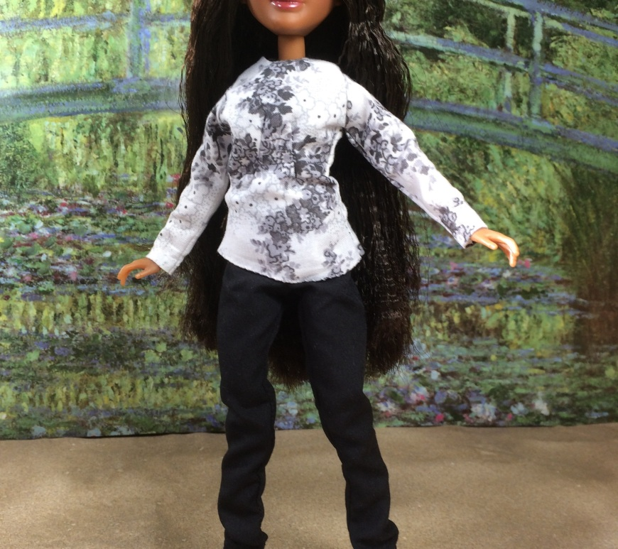 "Image shows the Bryden Bandweth doll from Project MC2 wearing doll clothes especially designed to fit her slender figure. She is posed on a sandy surface with Monet's green bridge from ""Bridge Over a Pond of Water Lilies"" in the background. The clothes worn by the Bryden Bandweth doll consist of a long-sleeved, grey-and-white floral top over a pair of simple black pants. At the bottom of the image, it says, ""ChellyWood.com: FREE printable sewing patterns and tutorials."""