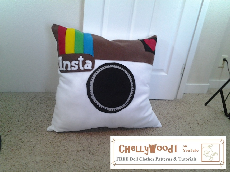 Image shows a very large pillow made of felt. It is designed to look like the retro Instagram logo.