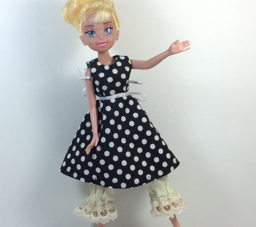"Click here for all the patterns and tutorials you'll need to make this dress: https: https://wp.me/p1LmCj-GOC The image shows a Disney Tinkerbell fairy doll wearing a handmade A-line sleeveless dress for tiny-body 8"", 9-inch, or 10 inch dolls like Disney Tinkerbell fairy dolls. In the diorama where the Disney Tinkerbell fairy doll stands, there's a tiny tea set on a wicker table, a wicker chair, and a bust of a musical composer resting on a pedestal. The patterns for making this A-line dress for Disney Tinkerbell fairy dolls are found at ChellyWood.com as a PDF downloadable sewing pattern. Chelly Wood designs free printable sewing patterns for making doll clothes to fit dolls of many shapes and sizes. Go to ChellyWood.com for both the PDF pattern and free tutorial video giving instructions for making this lovely dress which will fit Disney Tinkerbell fairy dolls and other similar-sized dolls."