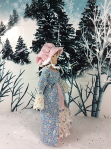 "Image shows a Breyer™ Doll wearing a pink ""pioneer-style"" bonnet and long Victorian dress with lace sleeves and a lacy petticoat. She walks through a snowy forest scene. At the base of the photo, a watermark states, ""ChellyWood.com: FREE printable doll clothes patterns and tutorials."""