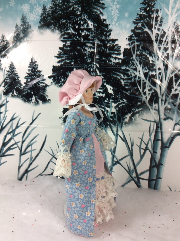 """Image shows a Breyer™ Doll wearing a pink """"pioneer-style"""" bonnet and long Victorian dress with lace sleeves and a lacy petticoat. She walks through a snowy forest scene. At the base of the photo, a watermark states, """"ChellyWood.com: FREE printable doll clothes patterns and tutorials."""""""