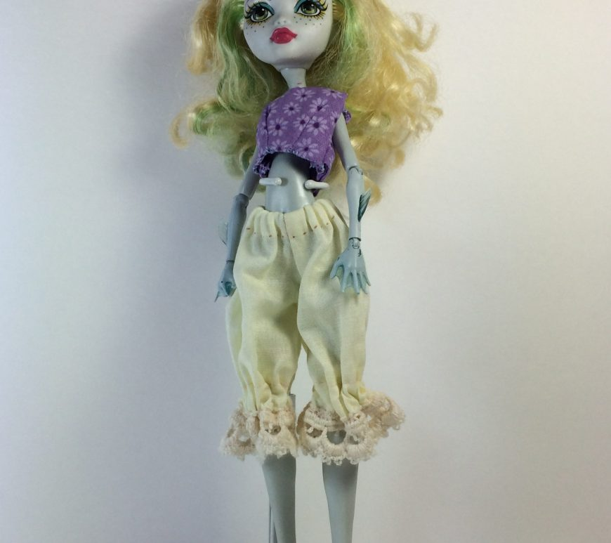 "Image shows Monster High Laguna/Lagoona Blue doll wearing a pair of lacy-bottom bloomers (pantaloons) and a purple crop top. Overlay says, ""ChellyWood.com: free printable sewing patterns for dolls of many shapes and sizes."""