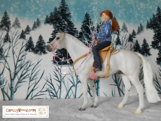 "Image shows Breyer horse Snowman (traditional sized horse) with rider. The rider wears a handmade plaid western shirt with collar and cuffs over elastic-waist handmade jeans. She is seated in a hand-made saddle and holds hand-made reins. The doll and horse are posed in a snowy countryside with a background of evergreen trees on a hillside. The watermark says, ""ChellyWood.com: free printable sewing patterns for dolls of many shapes and sizes."""