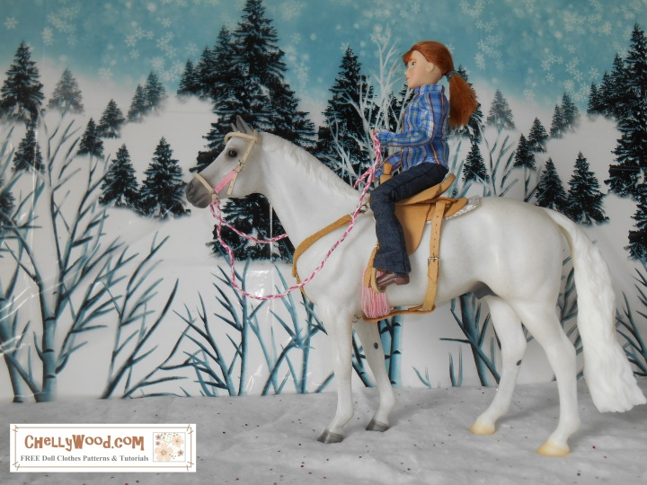 """Image shows Breyer horse Snowman (traditional sized horse) with rider. The rider wears a handmade plaid western shirt with collar and cuffs over elastic-waist handmade jeans. She is seated in a hand-made saddle and holds hand-made reins. The doll and horse are posed in a snowy countryside with a background of evergreen trees on a hillside. The watermark says, """"ChellyWood.com: free printable sewing patterns for dolls of many shapes and sizes."""""""
