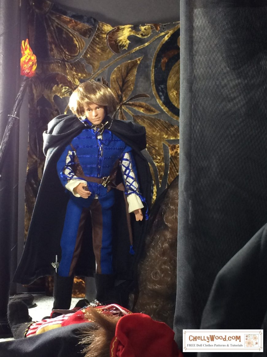 """Image shows Texas A & M Ken doll dressed in medieval clothing. He wears a black cloak. Above his head is a miniature torch, with its flame painted red, orange, and yellow. The doll stands over another male doll, whose face is obscured. The doll laying on the ground wears richly decorated Renaissance clothing with gold embroidery and a fancy muffin cap. The expression on the face of the Texas A & M ken doll is one of grief and regret. Part of the scene to the right appears to be obscured. This is a miniature """"Barbie and Ken"""" version of Romeo and Juliet, and we find ourselves looking at the scene in the tomb, when Romeo has just stabbed Tybalt. To learn more, please visit ChellyWood.com."""