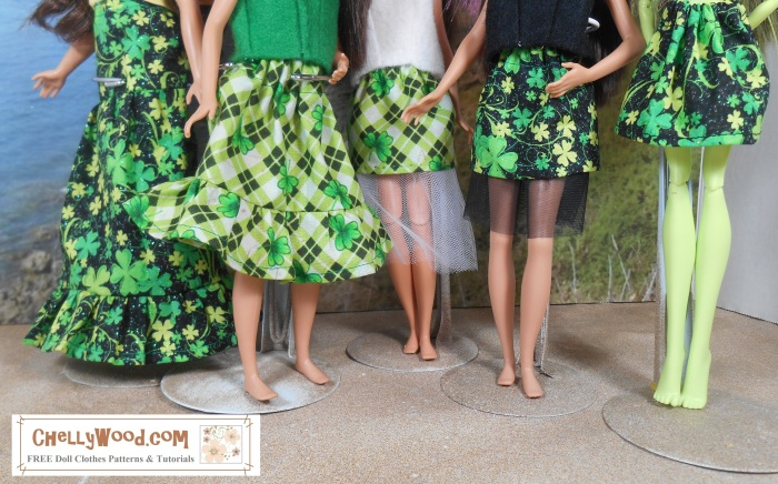 """Image shows five dolls wearing skirts ranging from a maxi skirt to a short miniskirt. Each skirt's fabric is made of St. Patrick's day themed print. Two of the skirts use a plaid green made with shamrocks. Three have shamrocks on a black and glittery background. The camera focuses on the skirts, not the dolls' shirts. The dolls are standing on a sandy surface, barefoot, with the ocean in the distance. It's a diorama background rather than a real-world one. A watermark in the lower-right corner says """"ChellyWood.com: free printable sewing patterns for dolls of many shapes and sizes."""""""