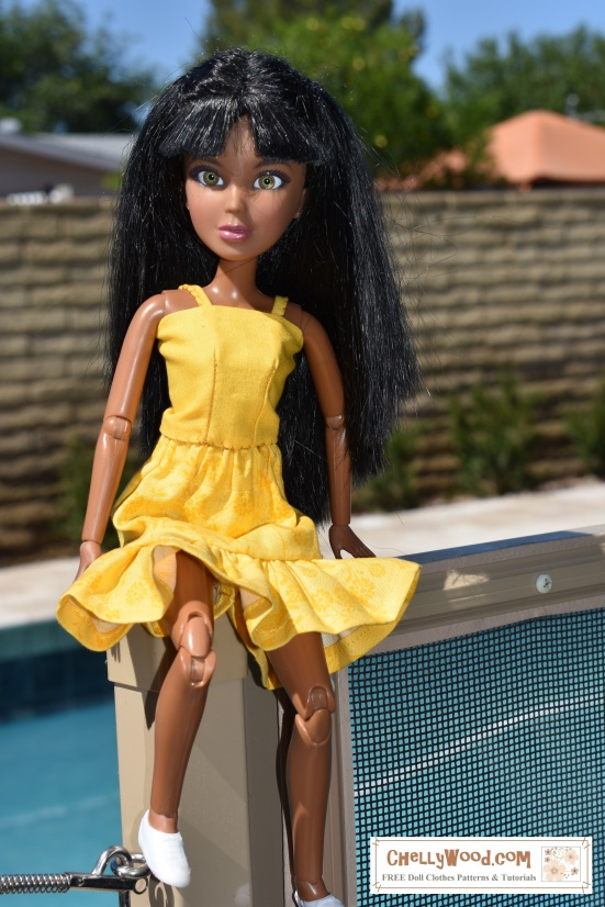 """Please visit ChellyWood.com for free printable sewing patterns. A Liv doll (11.5 inch fashion doll) is seen seated upon a fence wearing hand-made doll clothes. Behind her is a swimming pool. Overlay says, """"ChellyWood.com: free printable sewing patterns for dolls of many shapes and sizes."""""""
