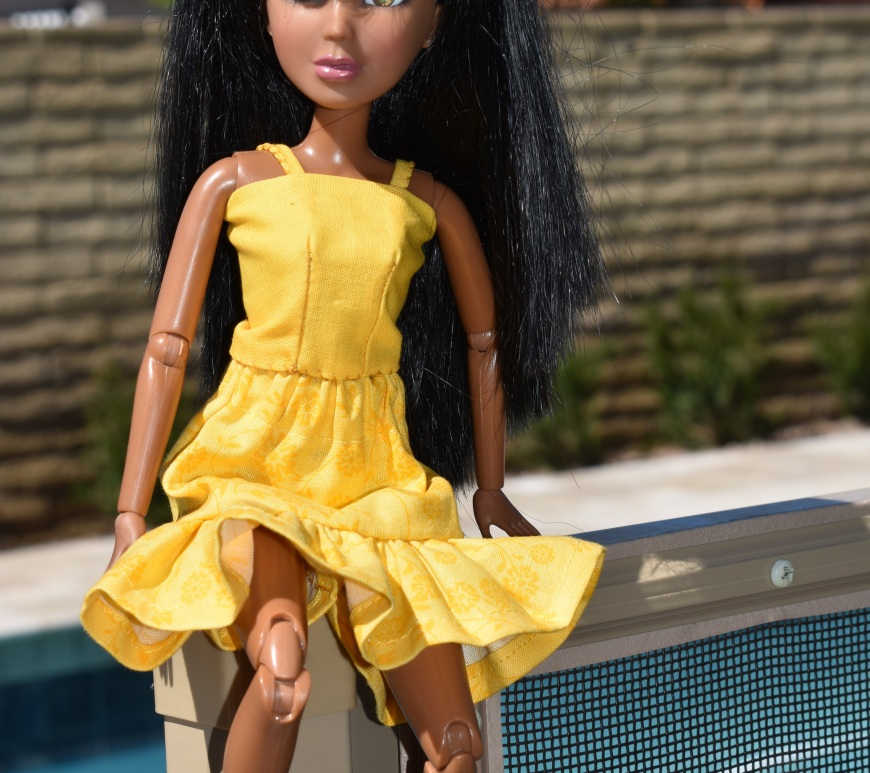 "Please visit ChellyWood.com for free printable sewing patterns. A Liv doll (11.5 inch fashion doll) is seen seated upon a fence wearing hand-made doll clothes. Behind her is a swimming pool. Overlay says, ""ChellyWood.com: free printable sewing patterns for dolls of many shapes and sizes."""
