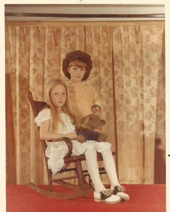 Image shows a young girl and boy dressed in old-fashioned clothes circa 1929. The girl is seated in a rocking chair, and she holds a ragged-looking Smokey Bear stuffed animal.