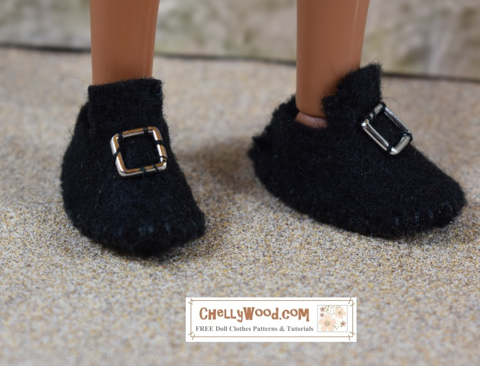 """Visit ChellyWood.com for free, printable sewing patterns for dolls of many shapes and sizes. Image shows a pair of Colonial-style shoes made of felt. Each black shoe has a longer-than-usual tongue and a silver buckle. The doll wearing these shoes is a Liv doll from spin master, but you can't see the doll's body--only her feet wearing the handmade felt shoes. She appears to be standing on a sandy surface. Overlay says, """"ChellyWood.com: free printable sewing patterns and tutorials."""""""