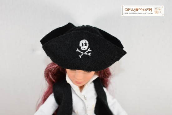 Visit ChellyWood.com for free, printable sewing patterns for dolls of many shapes and sizes. Image shows Project MC2 doll Camryn wearing a hand-made pirate hat made of felt with an embroidered skull and cross-bones (the Jolly Roger) on the front flap of the pirate's hat. Overlay offers the website ChellyWood.com for this free sewing pattern.