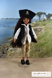 Please visit ChellyWood.com for free, printable sewing patterns to fit dolls of many shapes and sizes. Image shows the Bryden Bandweth doll from Project MC2 wearing a handmade pirate costume, which includes a tunic-like shirt, felt vest, felt Colonial shoes, cloth pantaloons, and a hand-embroidered pirate hat, which has the jolly roger embroidered on it. The doll stands on a sandy ground before a grassy knoll. Behind her is a large body of water. Overlay says: ChellyWood.com: free printable sewing patterns for dolls of many shapes and sizes.