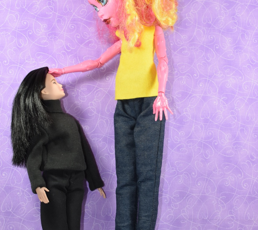 Image shows Monster High's Gooliope Jellington standing next to a Mattel Barbie dolls, to indicate the size difference. Gooliope Jellington stands at about 17.5 inches tall, and Barbies are typically 11.5 inches tall. In this image, Barbie looks up at the Monster High doll, while the taller doll places a hand on Barbie's head.