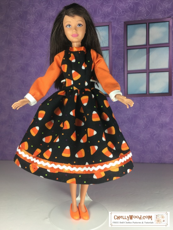 """Visit ChellyWood.com for free, printable sewing patterns for dolls of many shapes and sizes. Image shows a Mattel Skipper doll wearing an orange and black doll dress decorated with candy corns, ric rac, and ribbons. The skirt of the dress flares, and her long elegant sleeves end in a white cuff. Overlay says, """"ChellyWood.com: free printable sewing patterns for dolls of many shapes and sizes."""""""