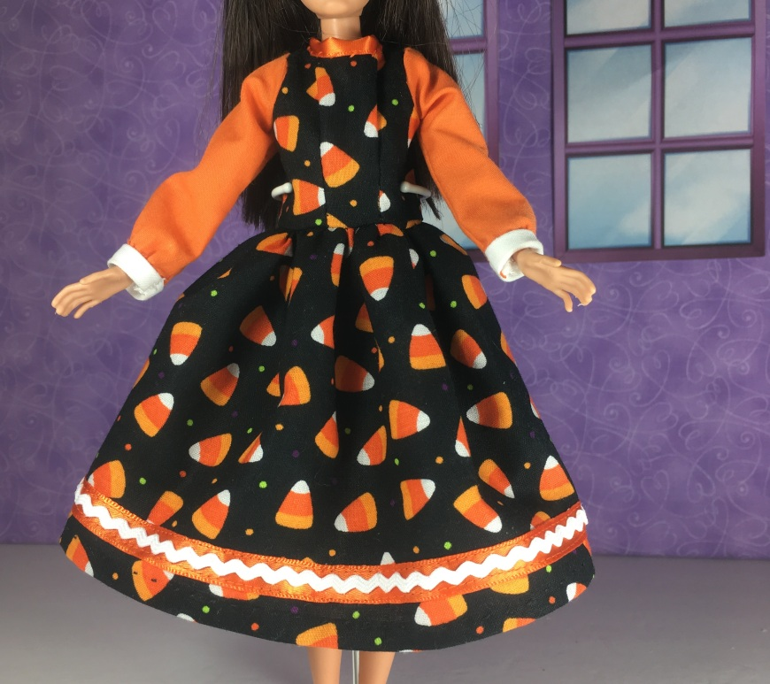 "Visit ChellyWood.com for free, printable sewing patterns for dolls of many shapes and sizes. Image shows a Mattel Skipper doll wearing an orange and black doll dress decorated with candy corns, ric rac, and ribbons. The skirt of the dress flares, and her long elegant sleeves end in a white cuff. Overlay says, ""ChellyWood.com: free printable sewing patterns for dolls of many shapes and sizes."""