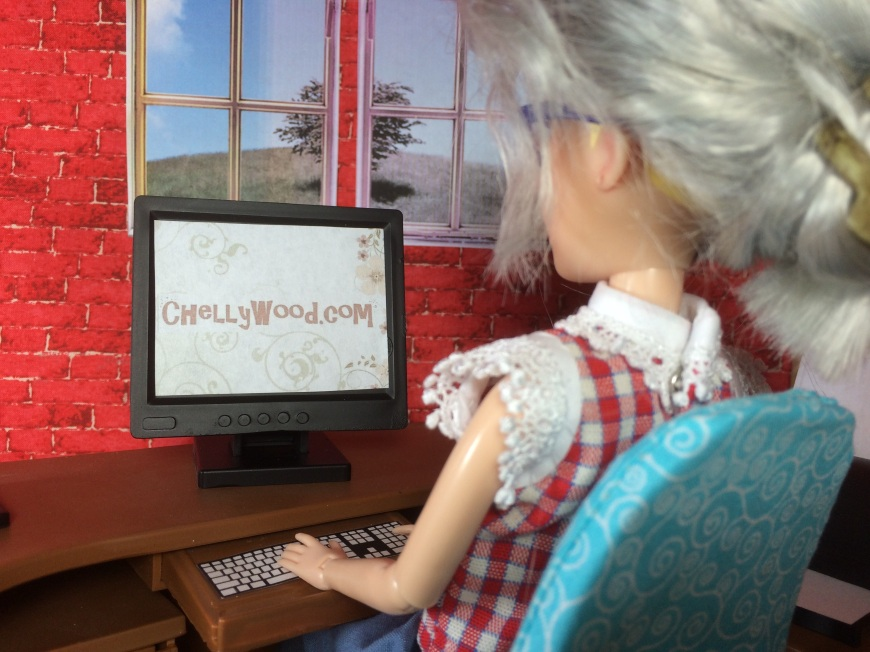 "Image shows a doll with gray hair worn in a messy bun. She sits at a computer that reads ""ChellyWood.com"" on the screen."
