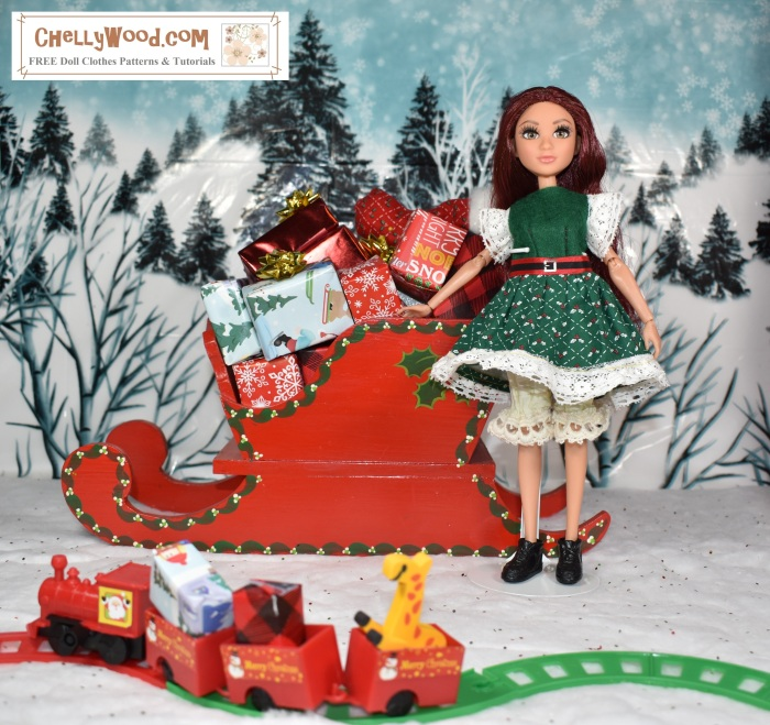 Please visit ChellyWood.com for free, printable sewing patterns to fit dolls of many shapes and sizes. Image shows a Project MC2 doll wearing a hand-made Christmas dress  and elf hat. She stands before a tiny train filled with gifts and toys. She leans against Santa's sleigh, which is filled with little wrapped gifts. Behind her is a snow-covered hill with many wintery pine trees.